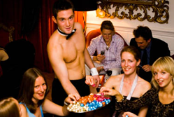 A topless waiter from Butlers in the Buff serving chocolates to a group of women