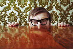Man hiding behind a table from the tax inspector