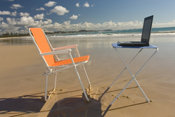 Deckchair and laptop on a beach