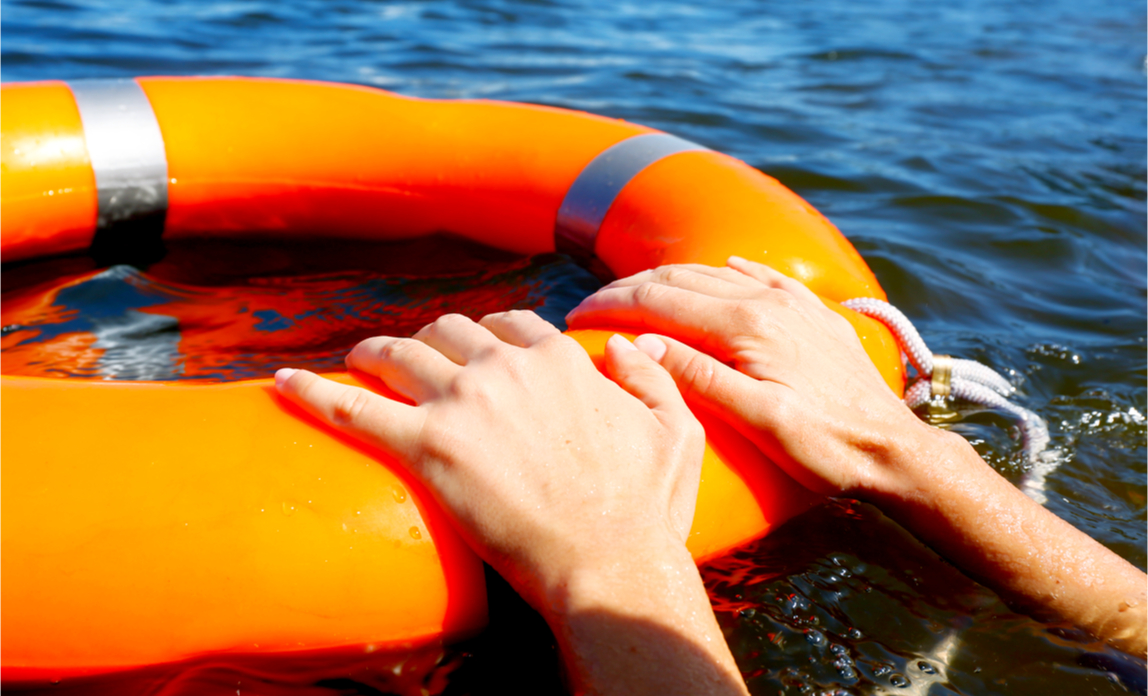 A woman's hands holding on to a life buoy to help ensure her survival