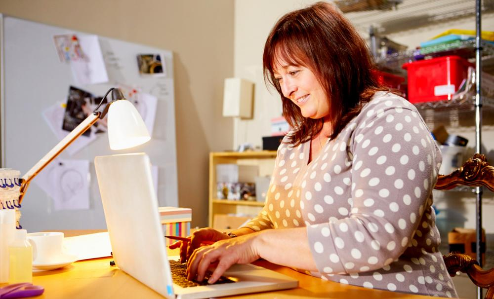 Middle aged women working from home on her laptop next to a table lamp