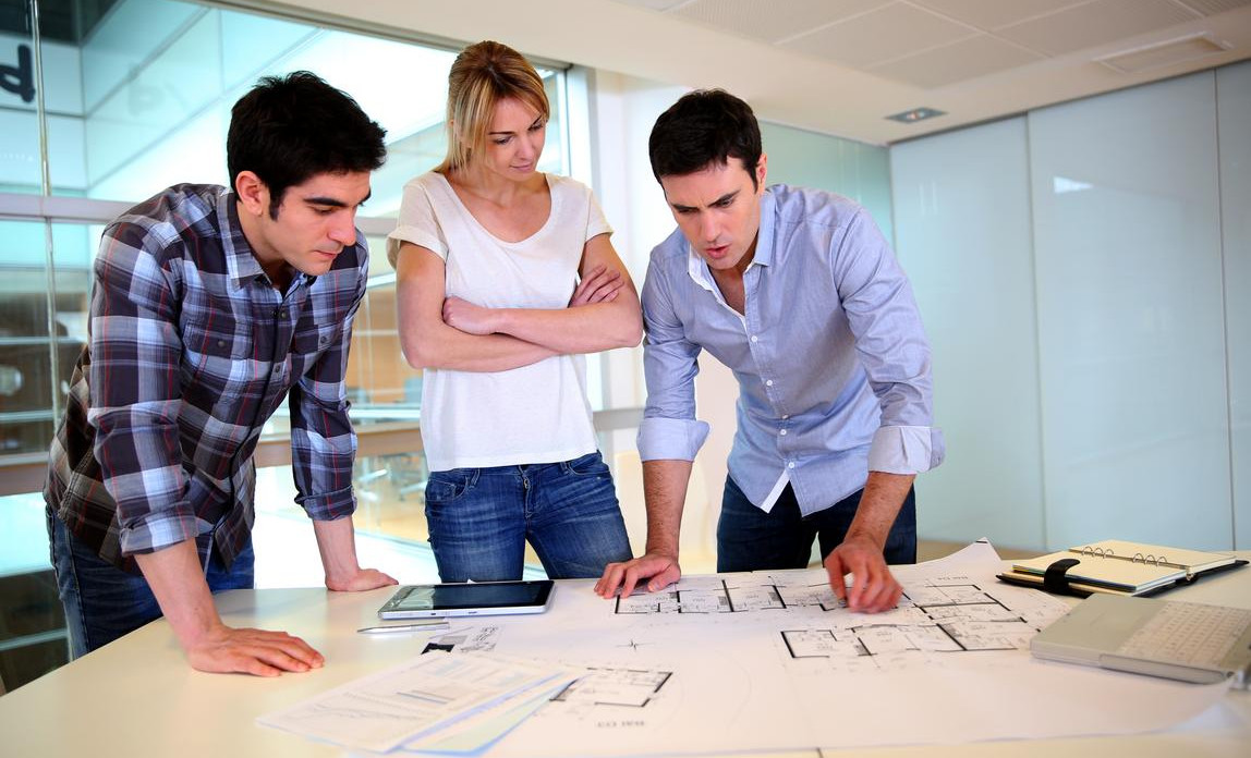 A group of architects looking over designs in their office