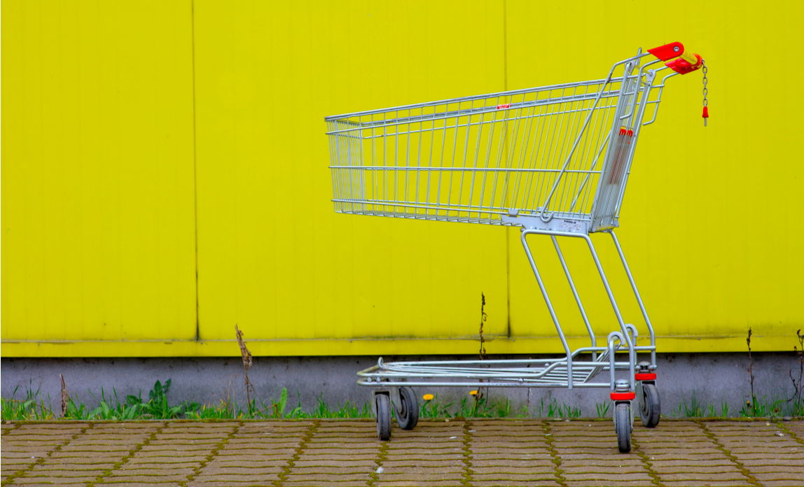 Abandoned shopping cart on yellow background