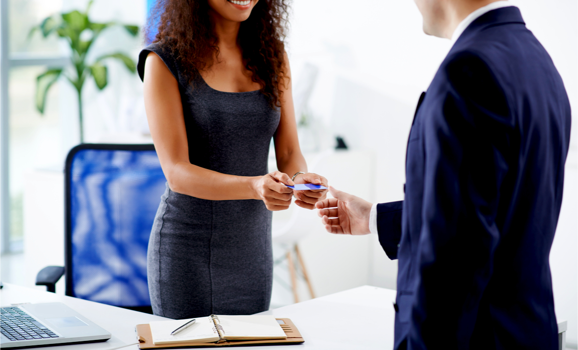 A smiling female entrepreneur proudly hands her new business card to a client.