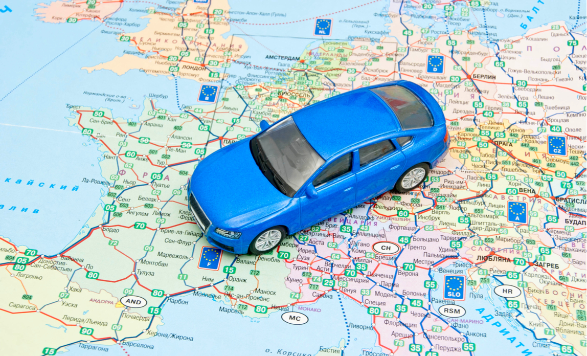 A blue toy car on a map of Europe