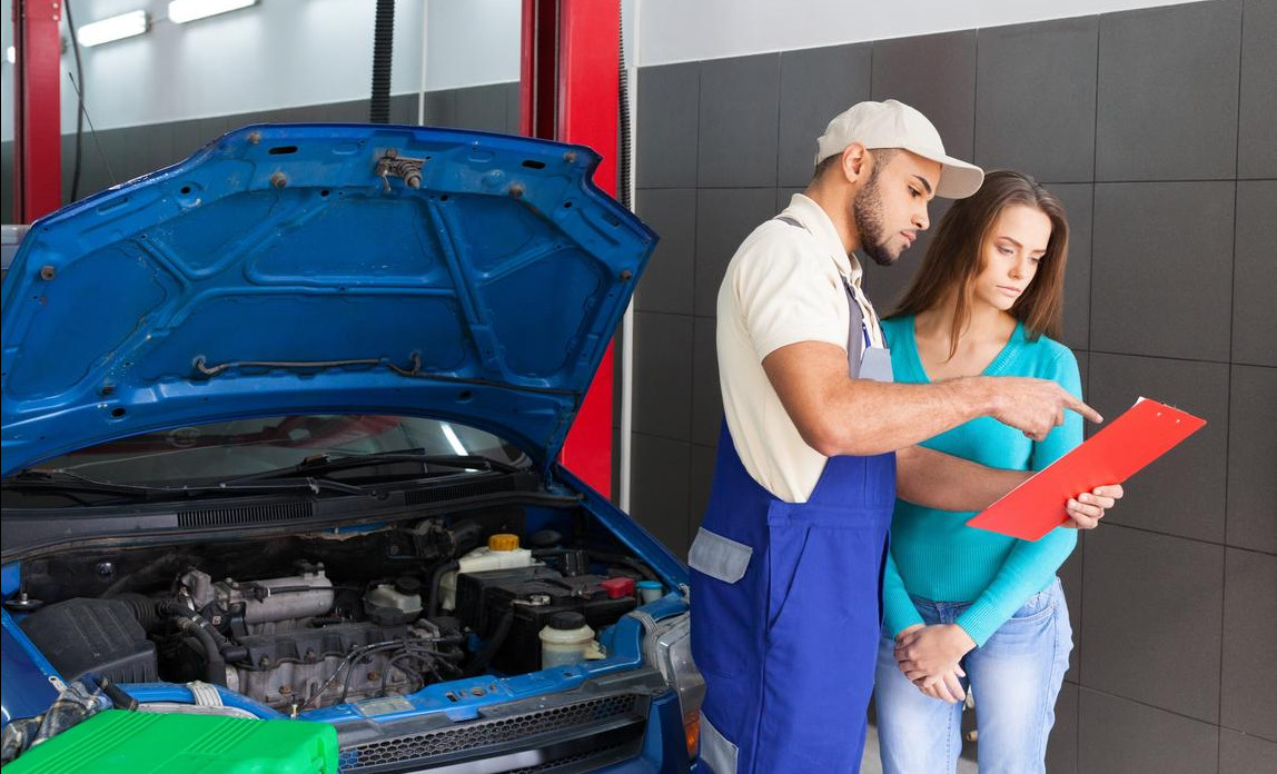 Car mechanic explaining the work needed to be done on a customers car
