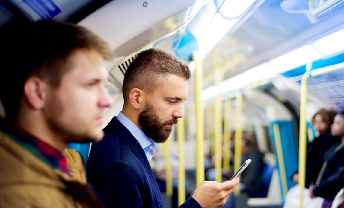 A businessman looks at his smart phone during a long commute