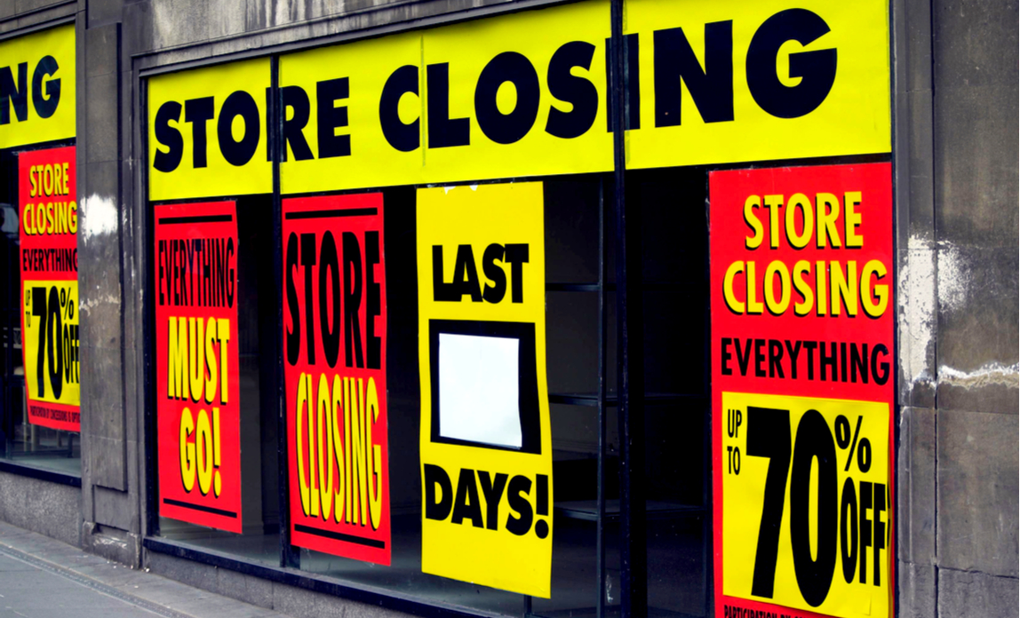 Store closing signs in a high street shop window