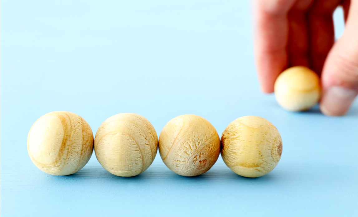 Hand arranging wooden beads illustration of creating an organisational structure