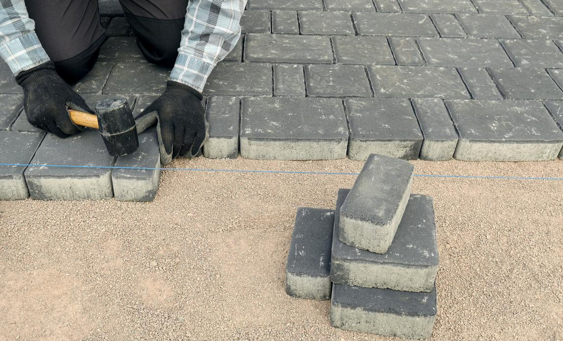 Sorting grey patio bricks for a driveway