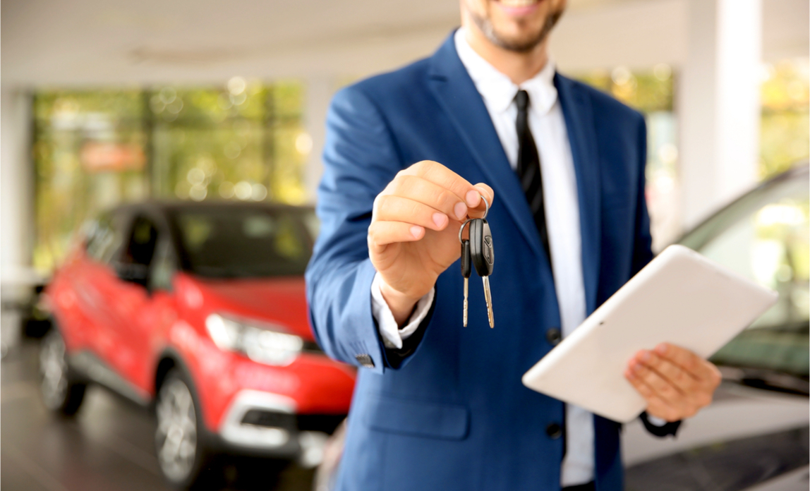 A car salesman hands over the keys to a new car