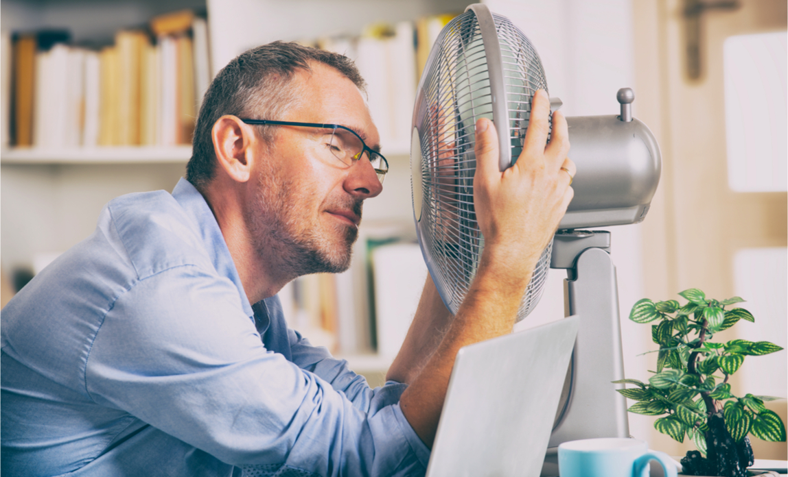 An office worker cools down using a fan at his desk.