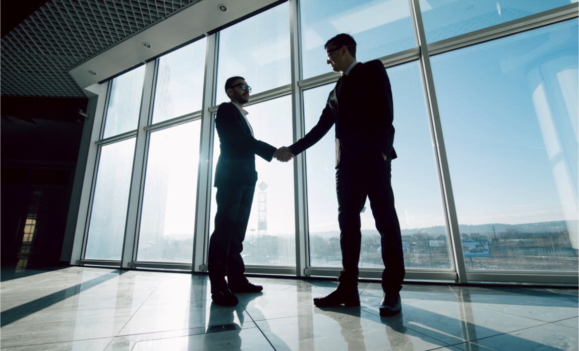An entrepreneur shakes hands with an estate agent, having found the perfect new office space.