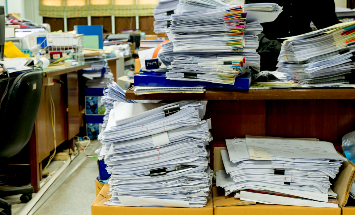 A cluttered office space full of paperwork that hasn't been properly filed.
