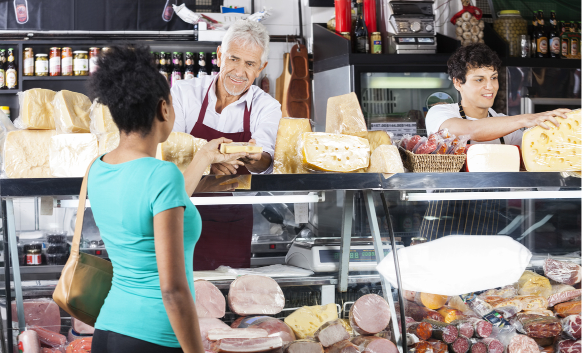 Two male retail assistants serve a female customer in a delicatessen's shop