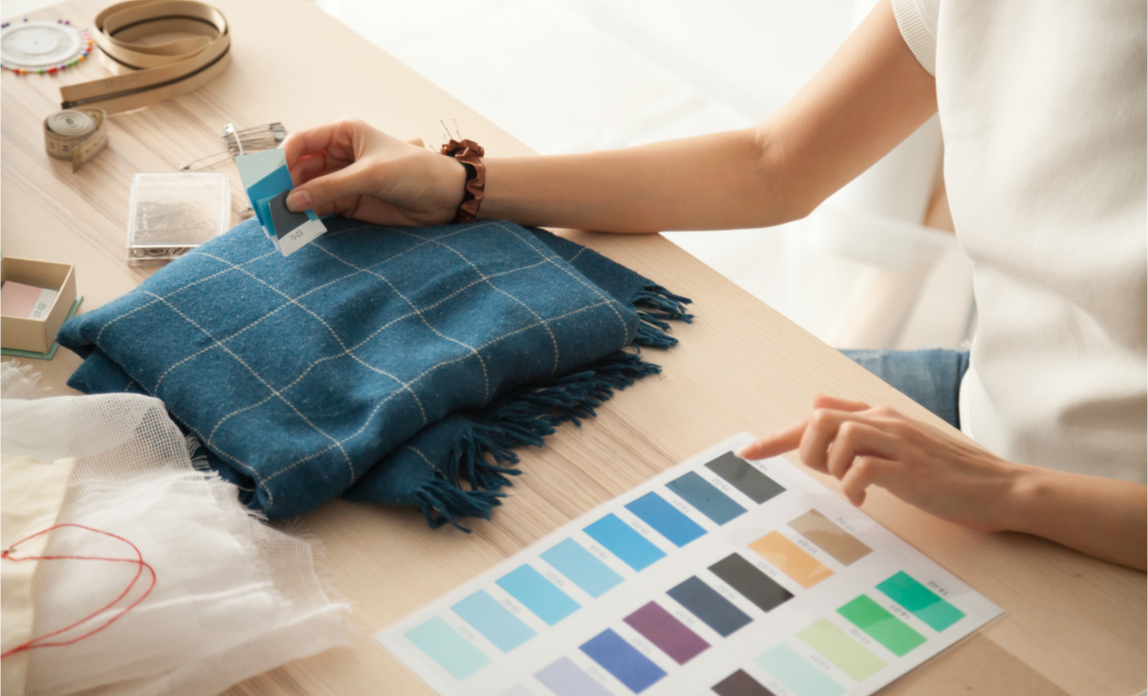 A small business owner plans the redesign of her business premises with colour swatches and fabric samples