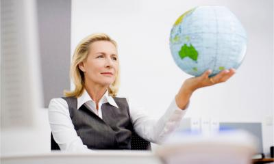 A businesswoman holds an inflatable globe