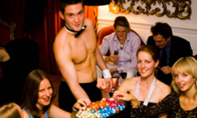 A topless waiter from Butlers in the Buff serving chocolates to a group of women{{}}