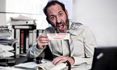 Angry man at desk - are you a terrible boss?