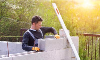 Builder using concrete blocks for building a wall at sunset