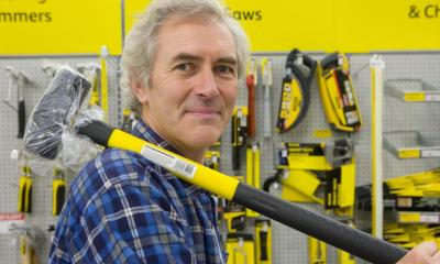 Builder holding yellow sledge hammer in hardware store