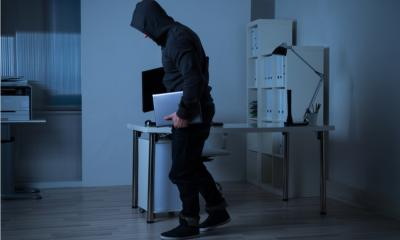 Man taking laptops from an office during the night