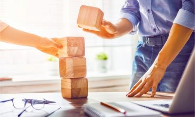Two businesspeople build a tower of wooden blocks