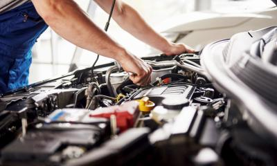 A mechanic looks under the bonnet of a car to assess the fault
