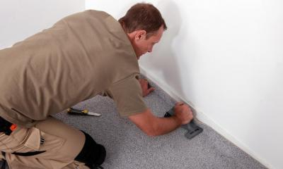 Carpet fitter fitting a carpet