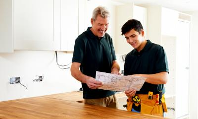Builder holding plans of work to show a customer