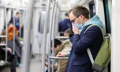 A male employee wears a face mask whilst communting to work to minimise the risk of contracting coronavirus