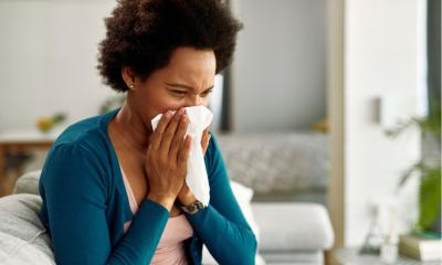 African American woman with flu virus blowing her nose at home