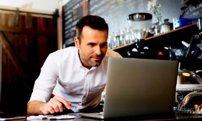 Cafe owner using his grey laptop to find out if he can franchise his business