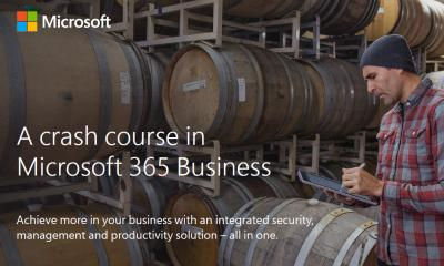Man in plaid shirt stood in front of wooden barrels for a Microsoft 365 Business advert