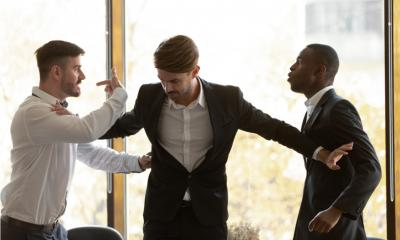 A manager separates two colleagues involved in an argument