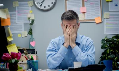 A stressed and exhausted worker is overwhelmed by paperwork in his office.