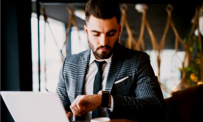 Bearded man in a suit looking at his watch while using his laptop