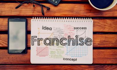 'Franchise' written on a notepad with a phone and glasses lying next to it