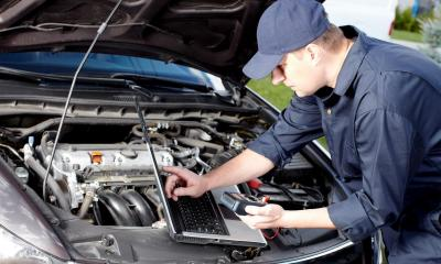 Car mechanic using a laptop as a OBD2 scanner tool
