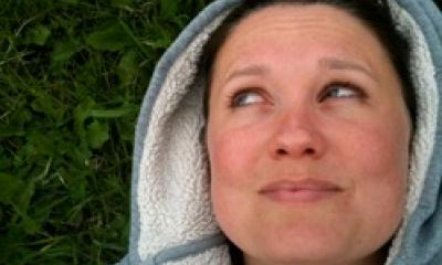 Hester moore lying back on grass while wearing a hoodie looking away from the camera