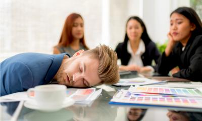 Man in a blue suit with his head on the table sleeping during a meeting