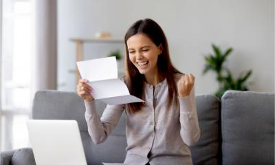 A happy female entrepreneur celebrates as she gets accepted for a small business loan