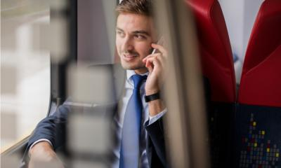 A business man talks on the phone whilst travelling on a train to a meeting