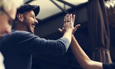 Man in a grey sweater and flat cap greeting another person with a high-five