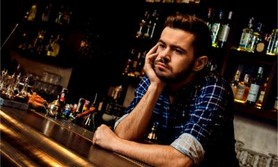 A bar manager is looking bored at work as his workplace is quiet