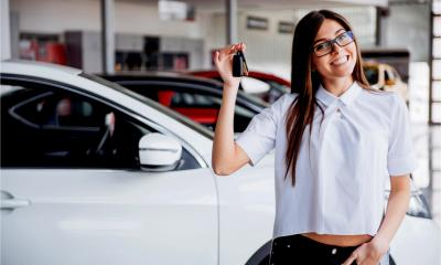 A fleet manager happily holds up the keys to a leased business vehicle.