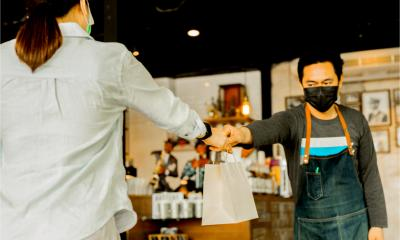 A waiter gives food to a client in a small food business. Social distance concept.