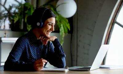 Smiling female manager in wireless earphones watches a training webinar on her laptop at home