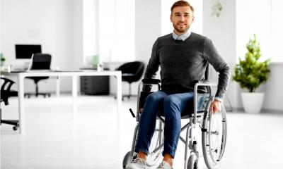 Young man in wheelchair at workplace