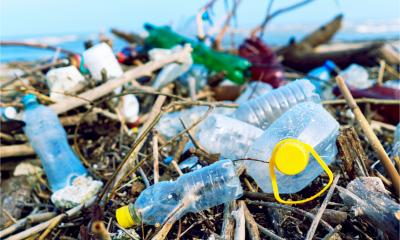 A pile of discarded plastic bottles and packaging that has been washed up on a beach - eco-unfriendly packaging concept.